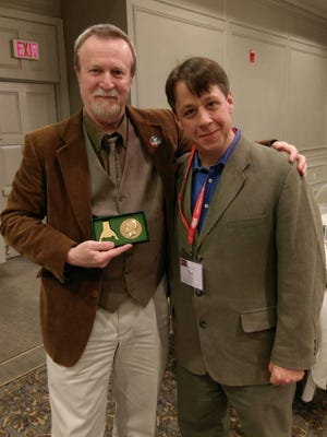 Tim Gleason, left, KNOW Theatre's artistic director, was awarded a medallion for his work at The Kennedy Center American College Theater Festival. At right is Ted Clement, incoming Region 1 co-chair for the festival.