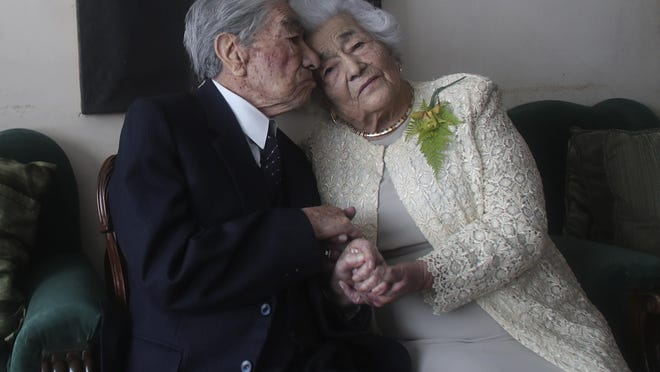 Julio Mora Tapia, 110-years-old and his wife Waldramina Quinteros, 104-years old, posse for a photo at their house, in Quito, Ecuador, Friday, Aug. 28, 2020.They have entered the Guinness World Records books as the oldest married couple in the world, after being together for 79 years. Guinness World Records has recognized them as the oldest married couple because of their ages, not because they have been married for eight decades.