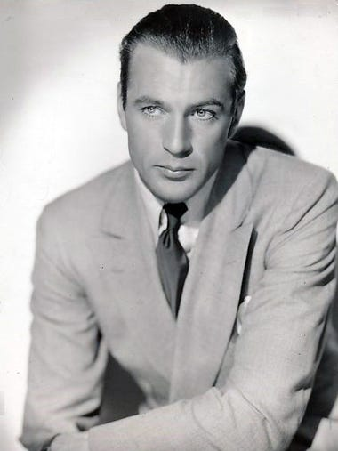 Gary Cooper poses in a studio publicity photo.