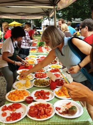Shoppers sample heirloom tomatoes at the Historic Lewes Farmers Market. Sales at the state's 25 markets surpassed $3 million in 2015, setting a record.