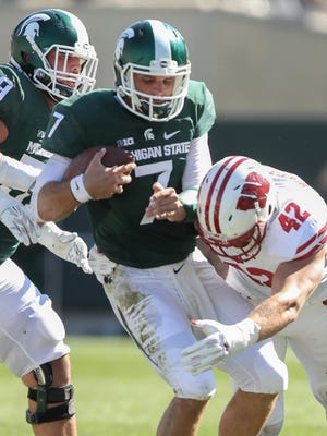 Michigan State Spartans quarterback Tyler O'Connor is sacked by the Wisconsin Badgers T.J. Watt during the second half Saturday, Sept. 24, 2016 at Spartan Stadium in East Lansing.