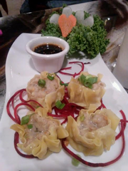 The Thai dumplings are a mixture of ground chicken and shrimp with shiitake mushrooms and cilantro in a steamed wonton.