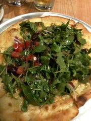 Station 49's arugula salad pie had crust baked with olive oil and Parmesan cheese. It is topped with a mound of bright and colorful balsamic vinaigrette-dressed tomato, arugula, red onion and black olive cold salad.