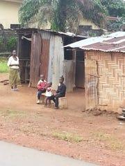 Children sit by the roadside in Monrovia, Liberia.