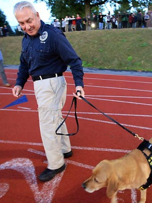 TSA agent David Wills and his explosive-sniffing dog Riverso attend the annual Joe Riverso memorial before Stepinac football game at Stepinac High School in White Plains on Oct. 11, 2014. Riverso, the dog was named after Joe Riverso, a White Plains man who was killed in the WTC on 9/11.