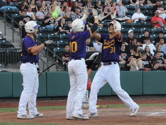 Roger Danison celebrates with his Bloom-Carroll teammates after scoring a run in the 2014 Division II state semifinal game at Huntington Park. The Bulldogs won the state championship the next day.