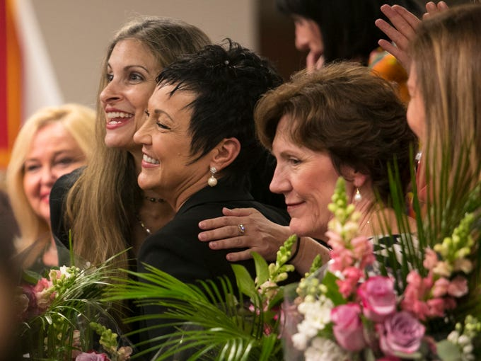 Kelly Fayer, left, and Teri Hansen embrace as they