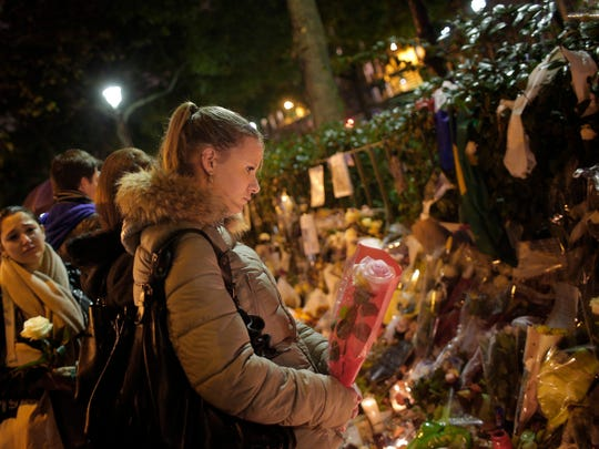 A woman pays respect Tuesday to the victims of the Paris terrorism attacks outside the Bataclan concert hall, which was a site of last Friday's attacks.