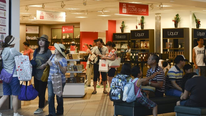 In this file photo, departing travelers look at products at Lotte Duty Free's retail space while others take seats on nearby benches at the A.B. Won Pat Guam International Airport.
