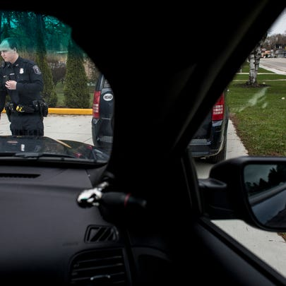 Police Officer Gordon Thomson walks back to his vehicle