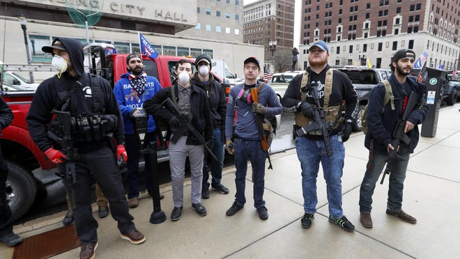 In this April 15, 2020 photo, protesters carry guns outside the Capitol Building in Lansing, Mich. A state panel on Monday banned the open carry of guns in Michigan's Capitol, a week after an armed mob rioted in the U.S. Capitol and following an attempt last year to storm the statehouse.