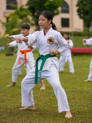Aiko Oku is photographed during a karate training session led by instructor Errol Lee at Matapang Beach Park in Tumon on April 11.