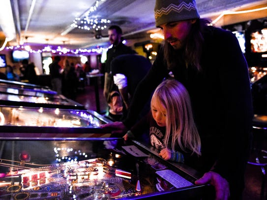 Tom Dillon helps his son Levon, 4, play a game at Pinball