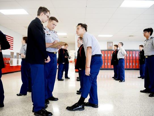 Alex Cojocari, left, and Michael Liepold conduct uniform