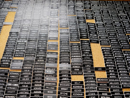 Name tags of past JROTC cadets line a cork board at