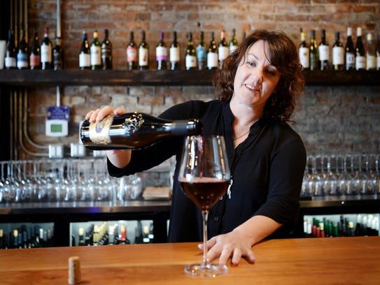 The District Wine Bar owner Lauri Nichols pours a glass