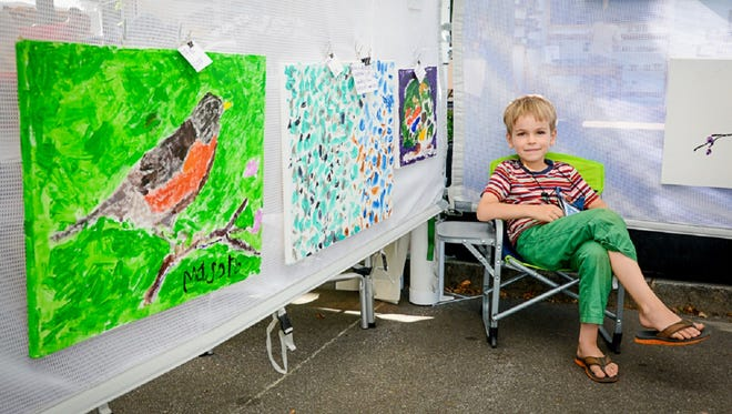 Mason McNabb, 6, and two of his paintings. The blue-and-white abstract sold at Art in the Park.