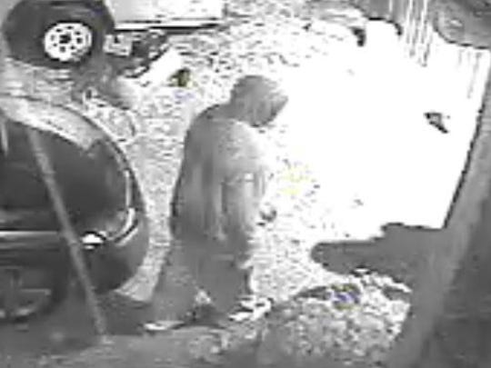 One of three masked men was shown away from the others in this surveillance image from a January home invasion.