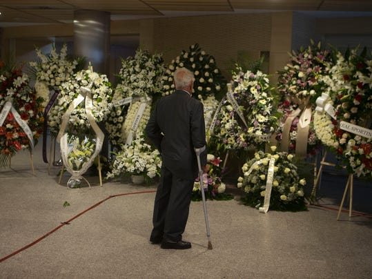 Emilio Butragueno, the father of former Real Madrid player of the same name, looks at flowers from other soccer clubs and well-wishers that were placed inside Real Madrid's Santiago Bernabeu stadium after the death of of Alfredo Di Stefano, in Madrid, Spain, Tuesday, July 8, 2014. Alfredo Di Stefano, the player Real Madrid has hailed as the most important component in its mid-20th century ascent to becoming a global football powerhouse,  died Monday after a heart attack. He was 88. Renowned for his speed, versatility and strategic grasp of the game, he helped Madrid attain five straight European Champions Cups and was voted European player of the year in 1957 and '59.(AP Photo/Paul White)