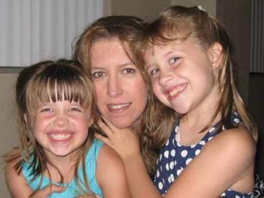 Michelle Mockbee with her daughters Madelyn, left, and Carli in 2009. Mockbee worked in human resources  at Thermo Fisher Scientific, where she was found dead in May 2012.