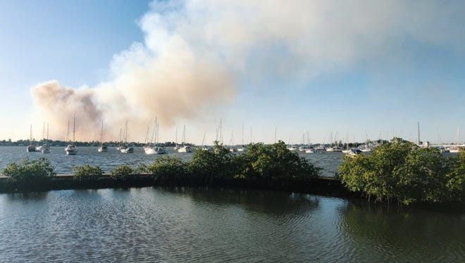 Smoke from a brush fire Wednesday, March 21, 2018, off Becker Road in St. Lucie County is seen from Shepherd Park in Stuart.