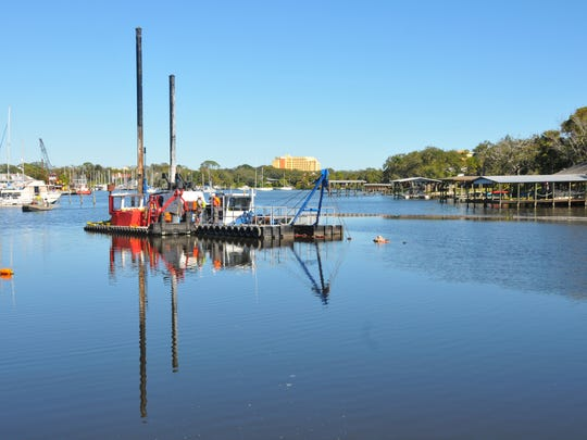 Workers put equipment in place for an Eau Gallie River Muck Dredging Project. The Brevard County Commission this week debated how much money from a special half-percent county sales tax should go toward muck dredging.