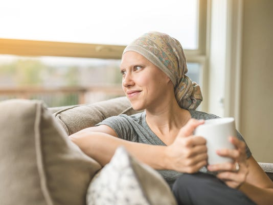 Ethnic young adult female cancer patient sipping tea