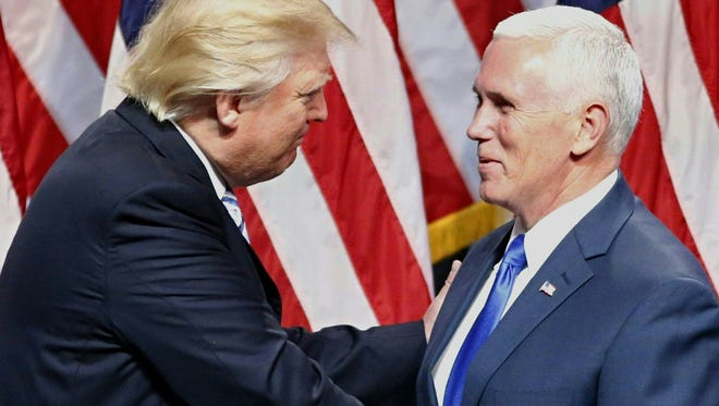 The GOP's presumptive presidential nominee Donald Trump shakes hand with his vice presidential running mate Indiana Gov. Mike Pence on July 16, 2016, during a press conference in New York.