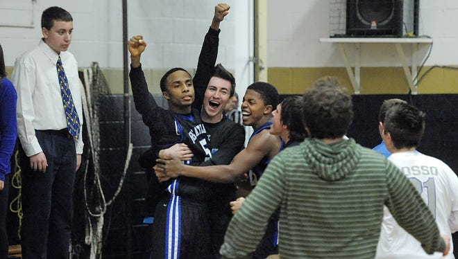 Wheatland-Chili's Tyler Roberts, arms raised at left, celebrates his game-winning basket with teammates and fans at Notre Dame High School in Batavia on Jan. 7, 2015.  Wheatland-Chili won 58-56 on a 3-point buzzer beater in overtime.