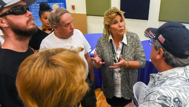 University of Miami's Florida Cancer Data System consultant Dr. Jill MacKinnon (center right) discusses the biological development of cancer with St. Lucie County residents Tuesday, June 12, 2018, during an open house to discuss glioblastoma cancer concerns within the community hosted by the The Florida Department of Health in St. Lucie in Bailey Auditorium at IRSC's Treasure Coast Public Safety Training Complex in Fort Pierce.