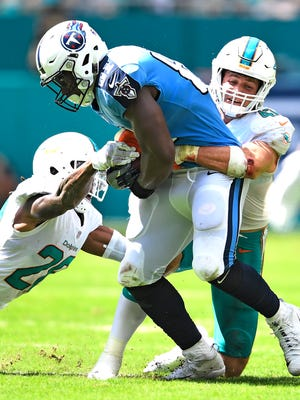 Titans tight end Jonnu Smith (81) holds onto a catch as Dolphins defenders close in during the second quarter at Hard Rock Stadium Sunday, Oct. 8, 2017 in Miami Gardens, Fla.