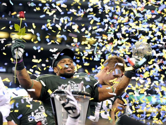 MSU's Denicos Allen and Connor Cook, behind, celebrate
