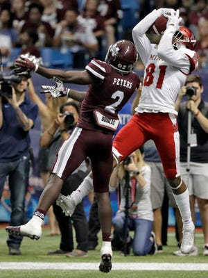 Miami wide receiver James Gardner pulls in touchdown pass in front of Mississippi State defensive back Jamal Peters during the first half of the St. Petersburg Bowl.