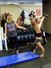 "In this Saturday, Feb. 18, 2017 photo, Associated Press writer Jenna Fryer, left, watches as Danica Patrick does a hand stand during a workout at Daytona International Speedway, in Daytona Beach, Fla. Patrick has launched a clothing line and now she has developed workouts and meal plans for a new book titled ""Pretty Intense.""."