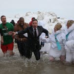 """Jimmy Fallon exits Lake Michigan with, from left, Chicago Public Library commissioner Brian Bannon, Chicago Park District CEO Mike Kelly and Chicago Bears defensive end Israel Idonije on March 2, 2014, in Chicago. Fallon participated in the """"Polar Plunge."""""""