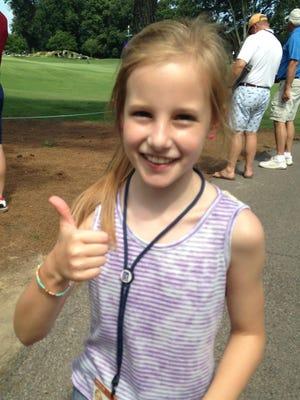 Anna Toms, 9-year-old daughter of David Toms, gives her approval after her dad holed a pitching wedge for an eagle during the second round of the FedEx St. Jude Classic in Memphis.