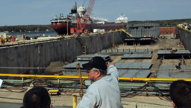 """During this year's Shipyard Tours, retired Bay Shipbuilding Co. employee and guide Bob Dvorak of Little Harbor explains the ATB (Articulated Tug Barge) """"Mississippi'' under construction in the large graving dock for Moran Towing for the oil/chemical industry. In the background is the famed Arthur M. Anderson which was the last vessel to have contact with the Edmund Fitzgerald before it sank in Lake Superior in 1975."""