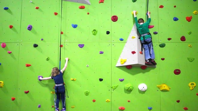 Kaitlin Furnish and David Shelton, both 6, attempt the climbing wall at Zip City.