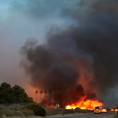 Firefighters battle flames Tuesday evening in Desert