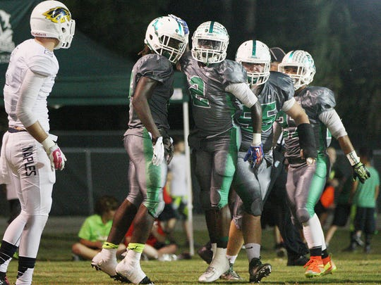 Fort Myers High School's Randy Smith (2), center, celebrates a touchdown against Naples last season at Fort Myers High School.