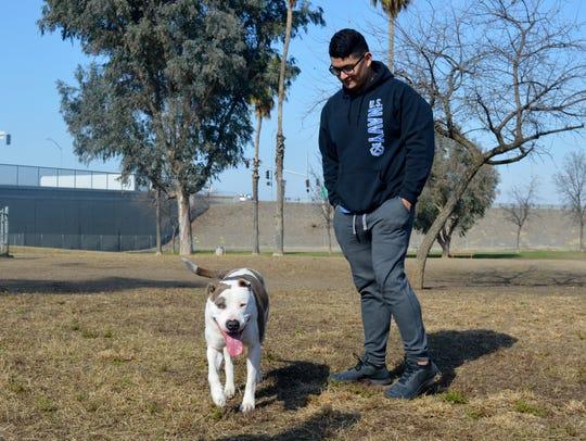 Rigo Nunez watches his dog Mia at Plaza Park's designated