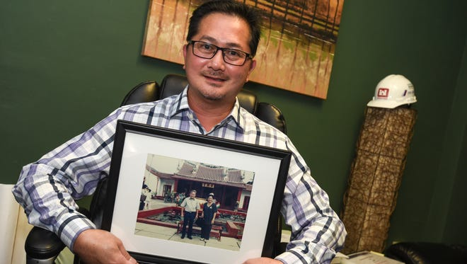 JMI-Edison Vice-President John Ilao, displays a photo of his parents and founders of Johndel International, Inc., John and Dely Ilao, while at his office in Tamuning on April 6, 2017.