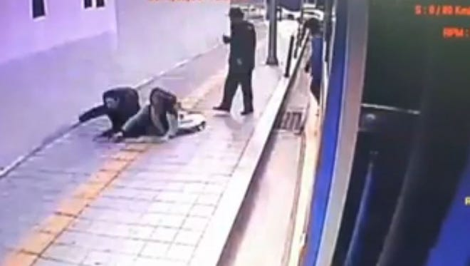 A man and woman were sucked into a sinkhole when they stepped off a bus in South Korea.
