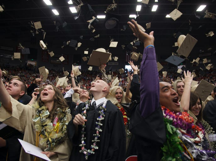 Desert Hills High School seniors toss their caps into the air at the end of their commencement exercises Wednesday, May 21, 2014 at Burns Arena in St. George.