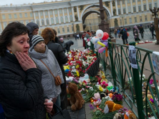 People look at photos of the plane crash victims attahced to the fence at Dvortsovaya (Palace) Square in St. Petersburg, Russia, on Monday, Nov. 2, 2015. In a massive outpouring of grief, thousands of people flocked to St. Petersburg's airport, laying flowers, soft toys and paper planes next to the pictures of the victims of the crash of a passenger jet in Egypt that killed all 224 on board in Russia's deadliest air crash to date.