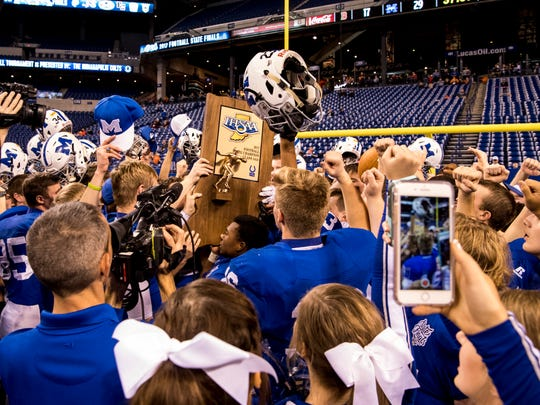 The Memorial Tigers receive the Class 3A State Championship trophy at Lucas Oil Stadium in Indianapolis, Ind., Friday, Nov. 24, 2017. The Tigers defeated the Braves, 29-17, to win the title.
