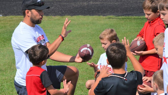 Former Western Michigan University quarterback Zach Terrell works with campers at the Young Stars Football Camp in Colon on Friday.