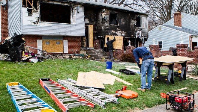 A fire damage restoration crew works on a home in the 200 block of Edjil Drive near Newark after it was destroyed by a fire on Monday morning.