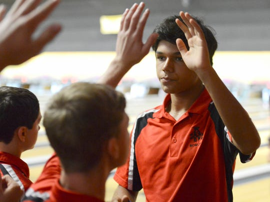 Theo Cox of Edgewood high fives teammates during bowling matches Thursday at Shore Lanes Merritt Island.