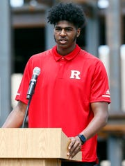 Myles Johnson, power forward for the Rutgers basketball team, towers over the podium at the topping off ceremony for new practice facility.